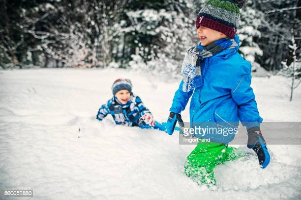 Little brothers playing in snow on a winter day