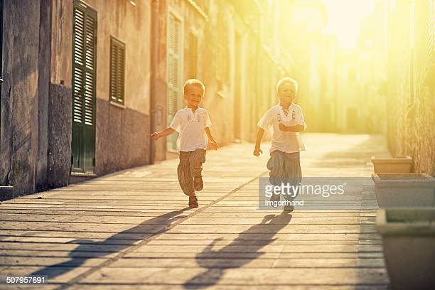 Little brothers running down a  mediterranean street