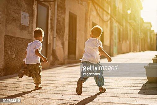 Little brothers running in a  mediterranean street