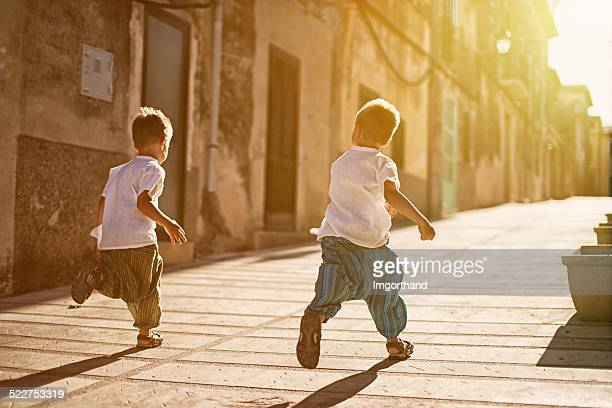 Little brothers running in a  mediterranean street