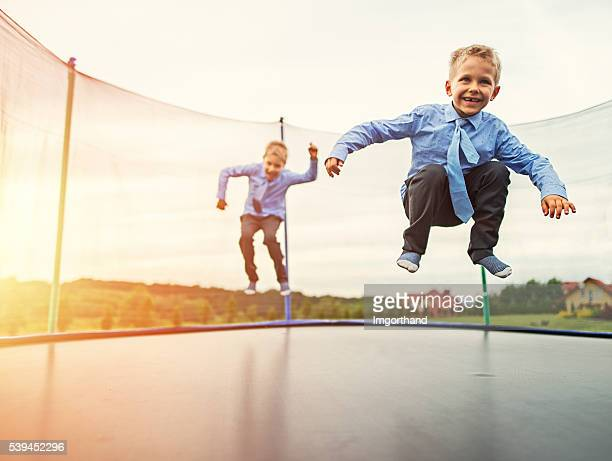 Little brothers wearing suits jumping on trampoline