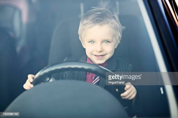 Little business boy driving to work.