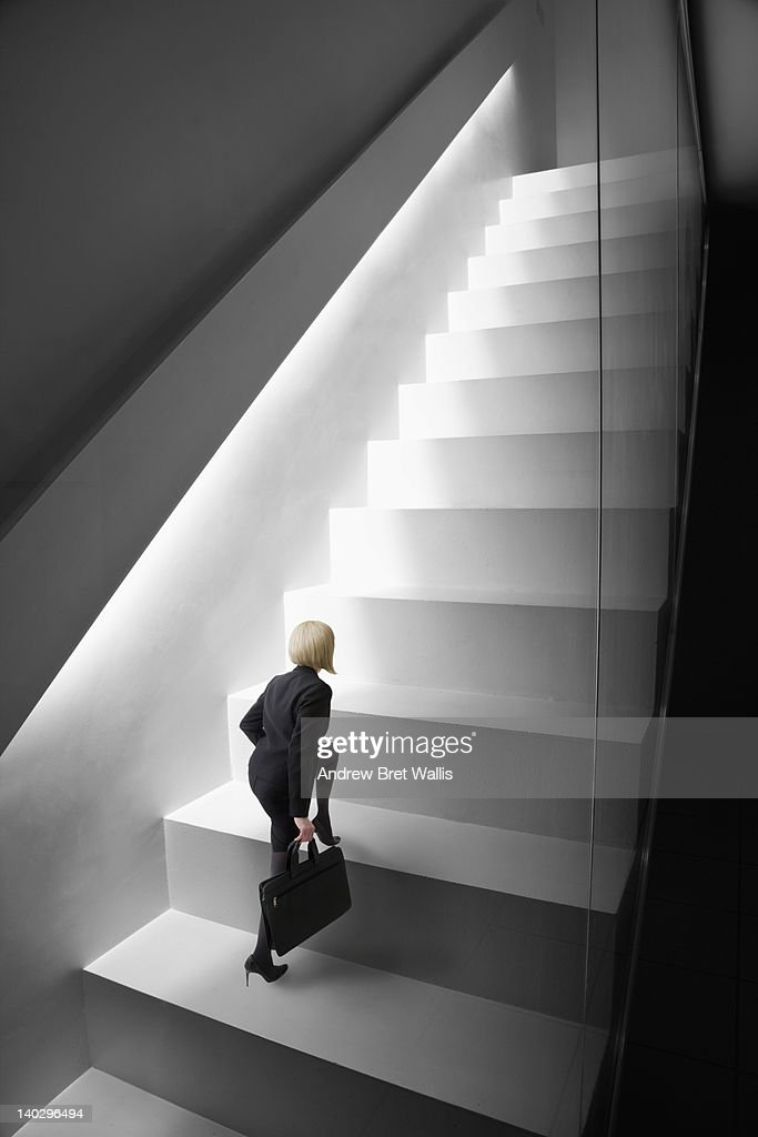 Little businesswoman climbs giant stairs : Stock Photo