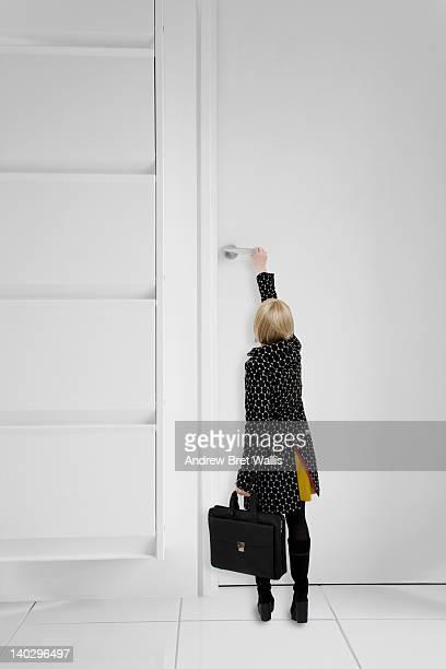 Little businesswoman reaches for giant door handle