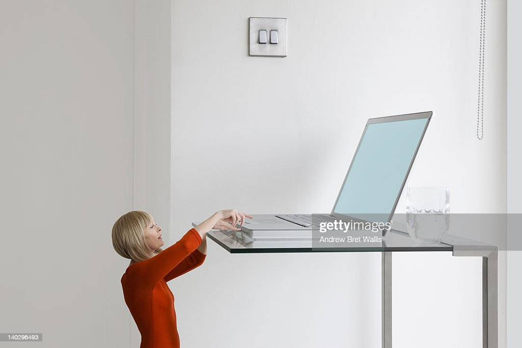 Little businesswoman reaches for giant laptop