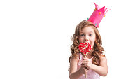Beautiful little candy princess girl in crown holding big pink heart lollipop and smiling