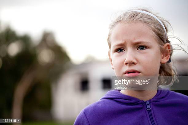 Little caucasian girl worried confused stressed outdoors