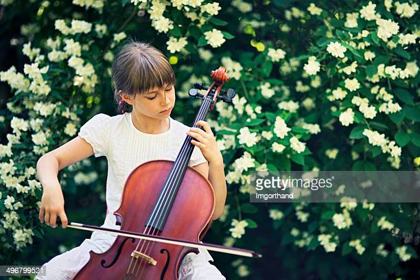 Little cellist playing in jasmine