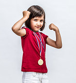 Little cheeky girl with medals smiling with strong arms raised, showing her young female power, motivation and winning success over a light grey background