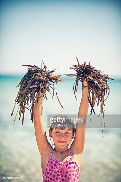 Little cheerleader playing with seaweed on the beach