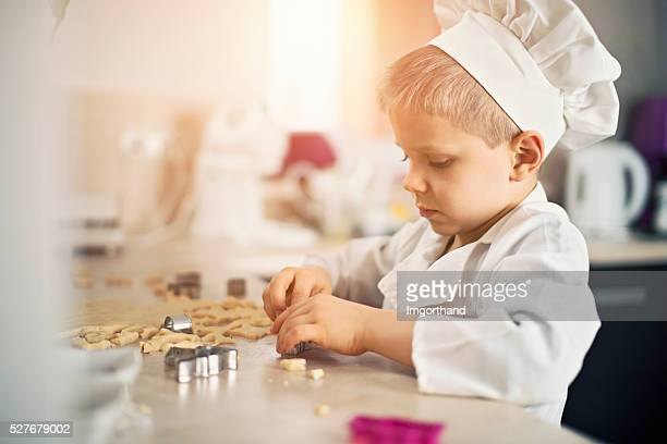 Little chef cutting out cookies in kitchen
