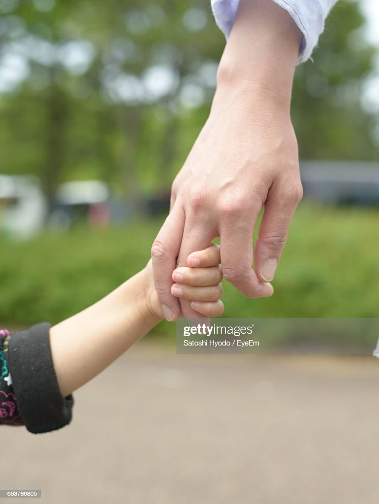 Little Child And Father Holding Hands