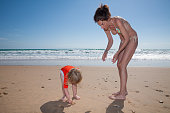 summer family of two years old blonde child with orange surf shirt and woman mother  in bikini picking sea shells at golden sand beach seaside