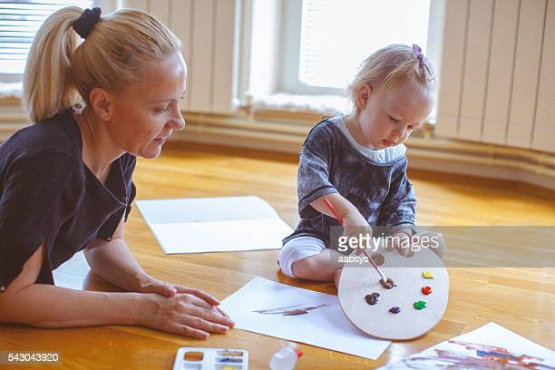 Little child and mother playing with colors and painting together
