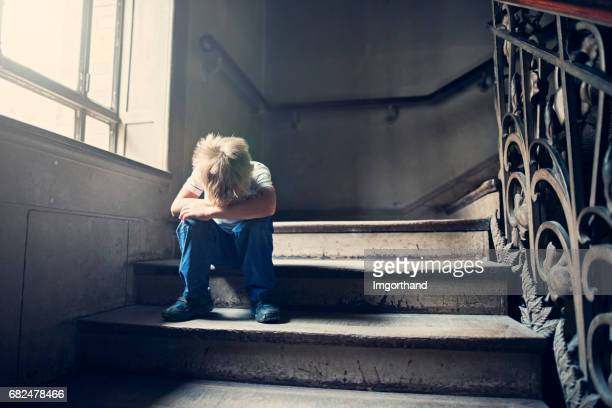 Kleines Kind weinend auf eine alte Treppe