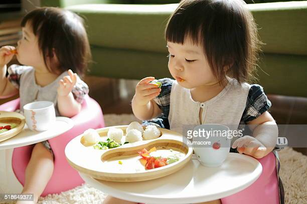 Little child eating meal in chair.