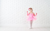 little child girl dreams of becoming  ballerina in a pink tutu skirt