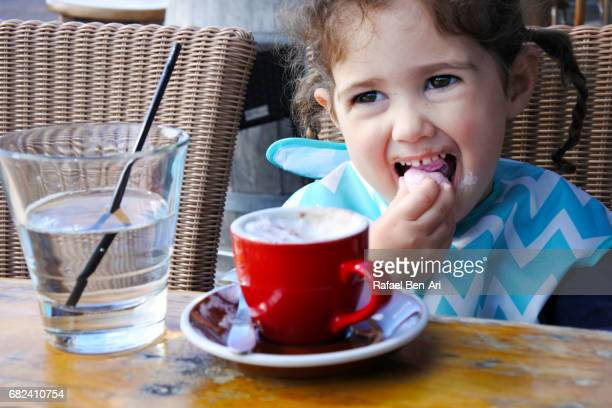 Little child girl drinks chocolate milk and and eats marshmallows
