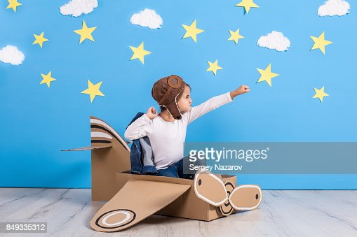 Little child girl in a pilot's costume is playing and dreaming of flying over the clouds : Stock Photo