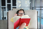 Little child girl with Glasses reading book in library, Education concept.