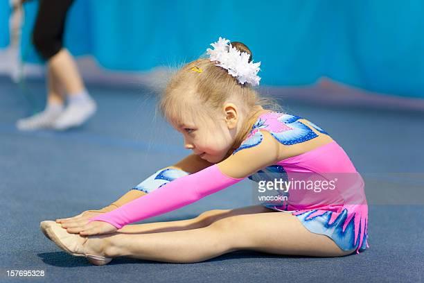 Little child gymnast doing exercise