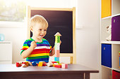 Little child playing with blocks. Boy building towers
