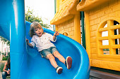 Cute little child plays on playground slide.