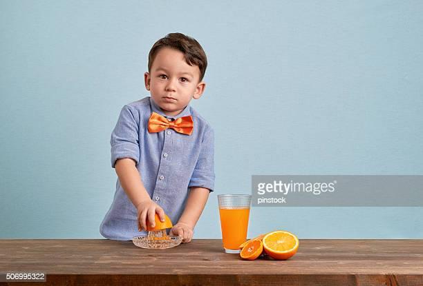 Kleines Kind die Zubereitung von frischen, hausgemachten orange juice