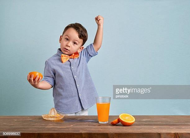 Little child preparing homemade orange juice