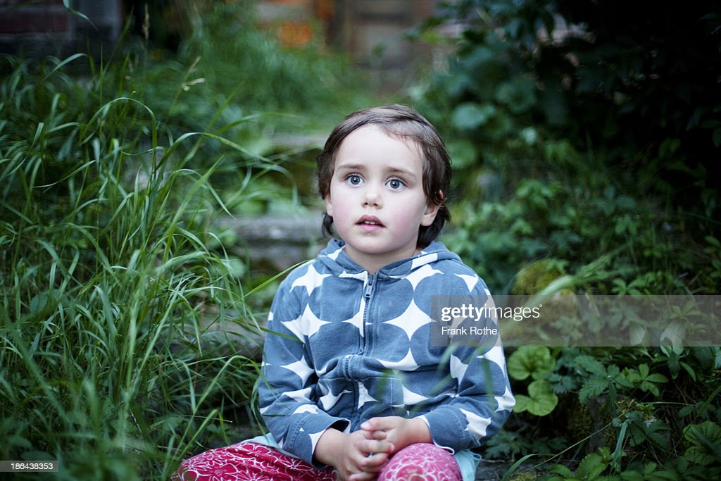 Little child sitting on stone steps in a green gar : Stock Photo