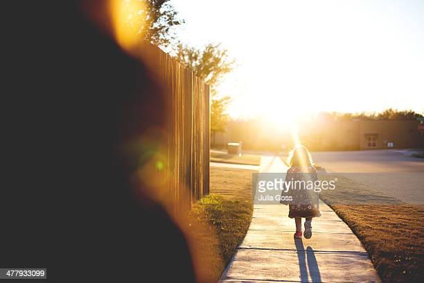 Little child walking into sunset