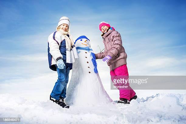 Kleine Kinder machen Schneemann.