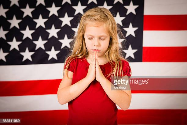 Little Christian Girl Praying in Front of American Flag