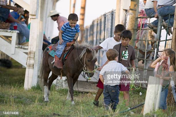 Little cowboys riding pony at PRCA Rodeo at Lower Brule Lyman County Lower Brule Sioux Tribal Reservation South Dakota 58 miles Southeast of Pierre...