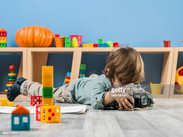 Little Cute Boy Using Camera In His Playroom