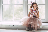 Little cute girl in beautiful dress is sitting near the window at home and blowing soap bubbles.