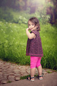 Little cute girl walking holding finger mouth