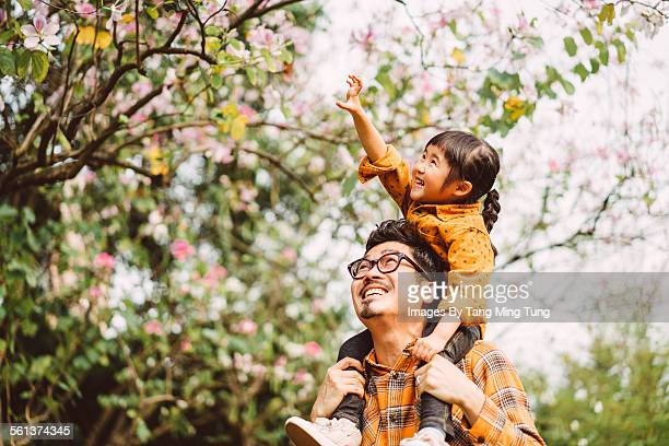 Little daughter riding young dad's shoulder