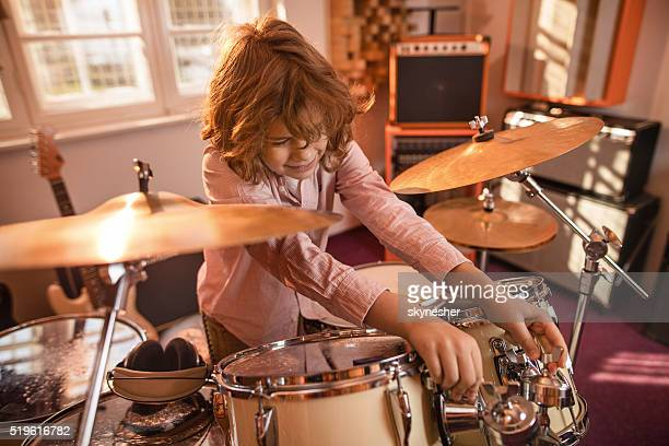 Little drummer adjusting drum kit in music studio.