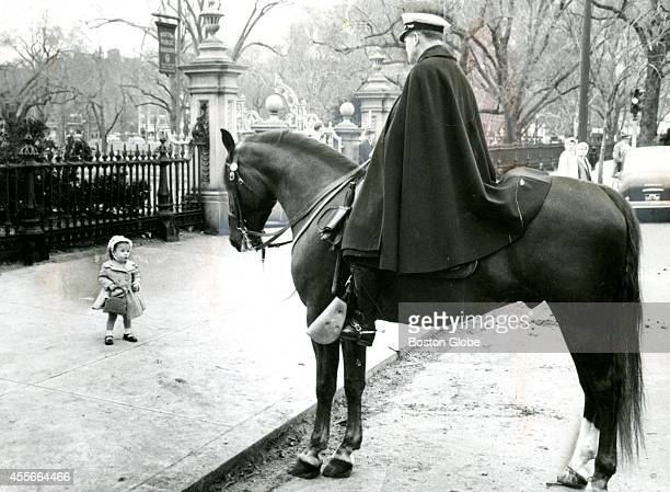 Little Elaine Martin in her Easter finery stopped to look at Officer Benjamin Donahue aboard his horse Justin's Son near the Boston Public Garden