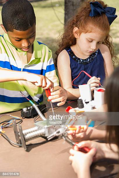 Little engineers! Multi-ethnic elementary children collaborate on 'robot' creation.