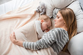 Top view of peaceful mother and cute child lying on double bed. They are sleeping together with tranquility