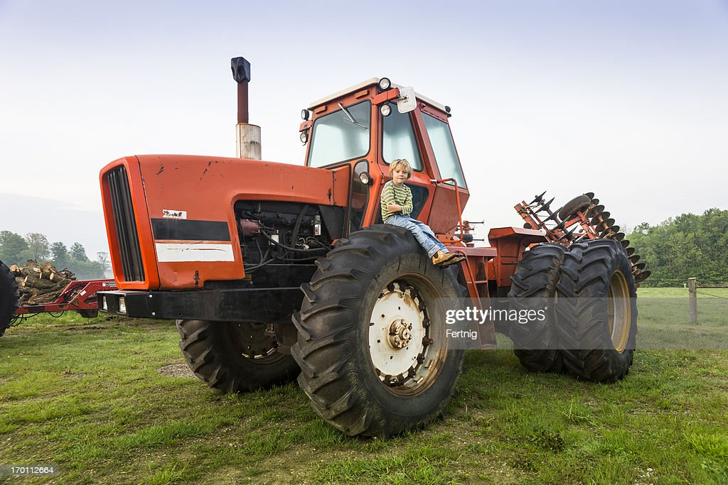 Boy On Tractor : Little farm boy on a tractor stock photo getty images