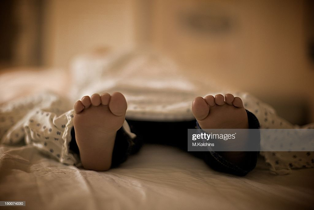 Little feet sticking out of blanket : Stock Photo