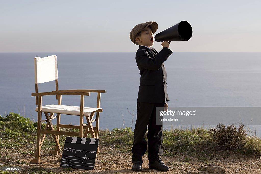 Little Film Director Shouting On Megaphone In Outdoor Set