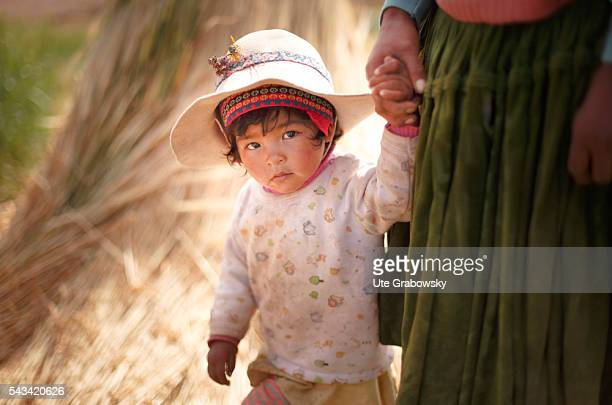 Little girl a farmer's child at her mother's hand in the Andes of Bolivia on April 15 2016 in Sacaca Bolivia