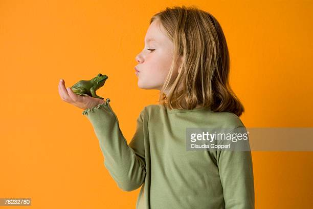 little girl about to kiss a frog