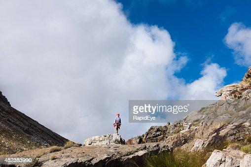 Little girl all alone on mountain peak in wilderness