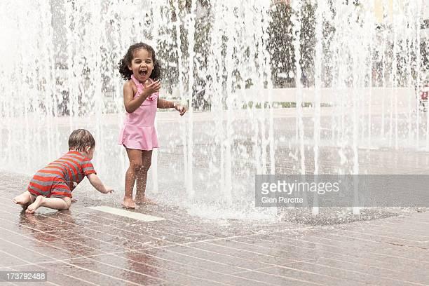 Little girl and baby boy having fun in fountain