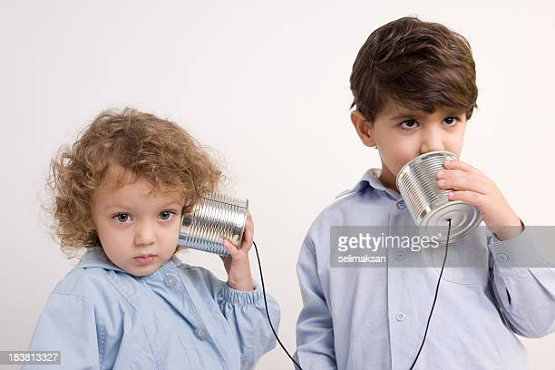 Kleine Mädchen und Jungen, die Kommunikation Via Dosentelefon